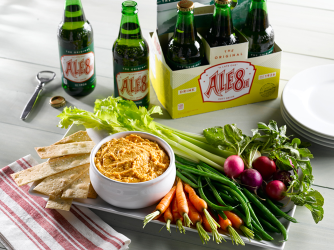 A bowl of beer cheese, surrounded by raw veggies, sits in front of a six-pack of Ale-8-One