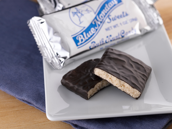 Wrapped and unwrapped Blue Mondays chocolate bars sit on a white plate