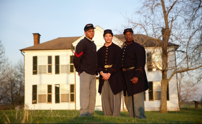 African American Civil War reenactors stand in front of a historic building at Camp Nelson National Monument