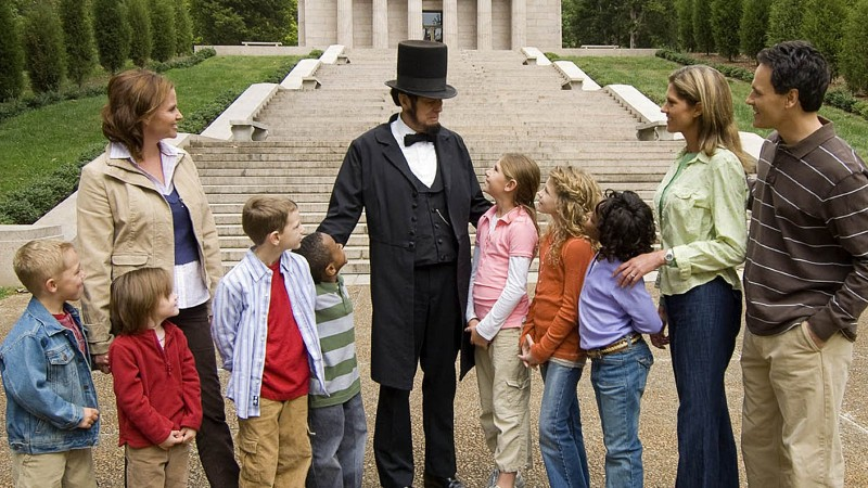 An Abraham Lincoln reenactor stands with a group of children at Abraham Lincoln Birthplace National Historical Park