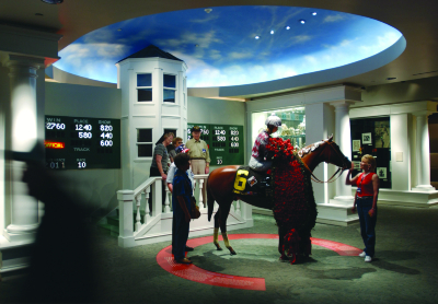 Visitors engage with the Winner's Circle exhibit at the Kentucky Derby Museum at Churchill Downs