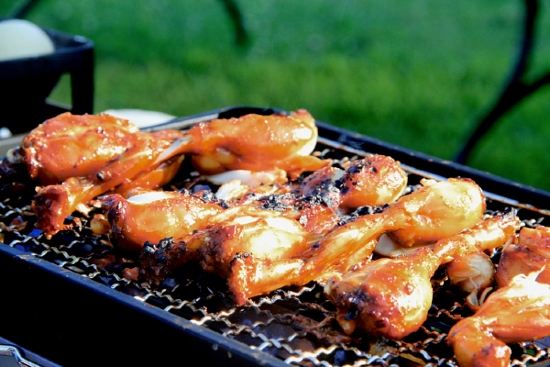 A shot of chicken, slathered in BBQ sauce, sizzling on an outdoor grill