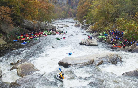 People kayak through rapids at Russell Fork as others look on