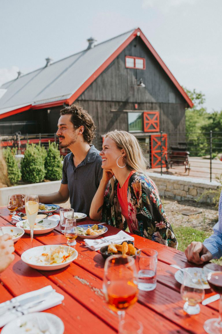 Couple dinning outside in front of a barn
