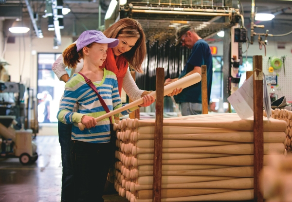A mother and daughter visit the Louisville Slugger factor, where the girl holds a newly made bat