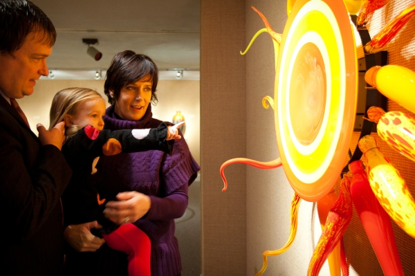 A mom and dad hold their young daughter as she points at a piece of art at Owensboro Museum of Fine Art (OMFA)
