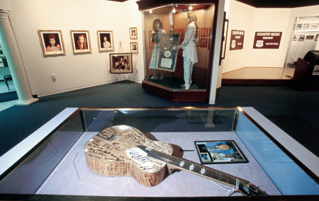 A country music exhibit at the Highlands Museum in Ashland, KY, displays a signed guitar and other memorabilia