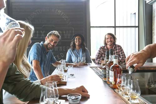 A group of people enjoy bourbon at a distillery in Bardstown, KY