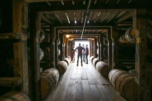 A person stands at the end of a long row of bourbon barrels at a Kentucky distillery