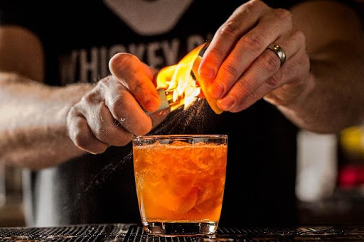 A bartender prepares a local bourbon craft cocktail, with fire