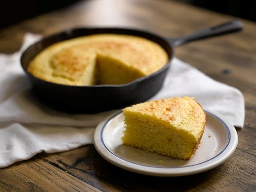 A freshly baked skillet of spider cornbread with a slice cut out.