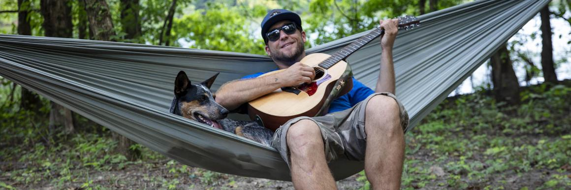 Adam Glick sits in a hammock with a guitar on location in Kentucky