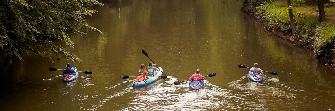 A group of people paddle down a Kentucky river