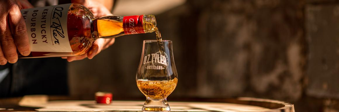 Pouring OZ Tyler bourbon into a glass