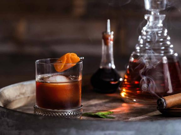 An Old Fashioned in a rocks glass, garnished with orange peel