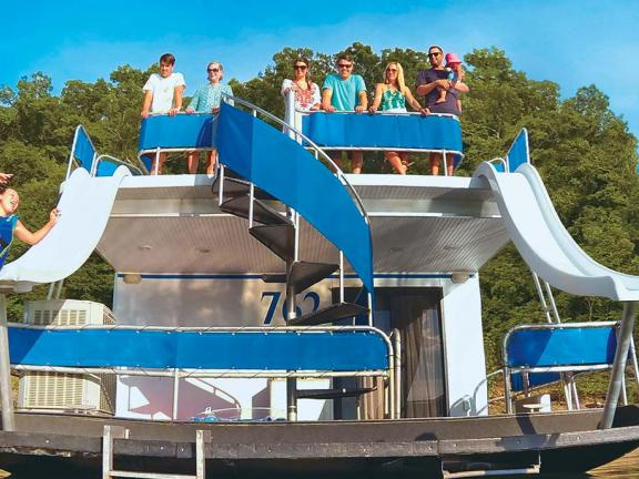 Kids slide off a waterslide on the back of a houseboat at Kentucky's Lake Cumberland
