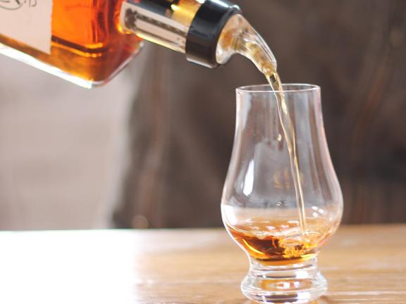 Bourbon pours into a tasting glass at Bluegrass Distillers in Lexington