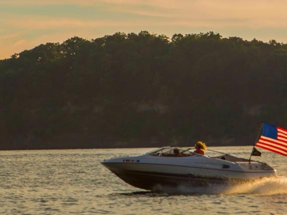 A speedboat flying an American flag speeds along the water at Lake Cumberland