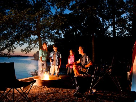 A family gathers around a campfire at a Kentucky campsite at night