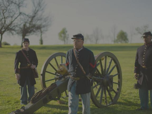 An African American man in Civil War-era uniform standing before a cannon during a reenactment