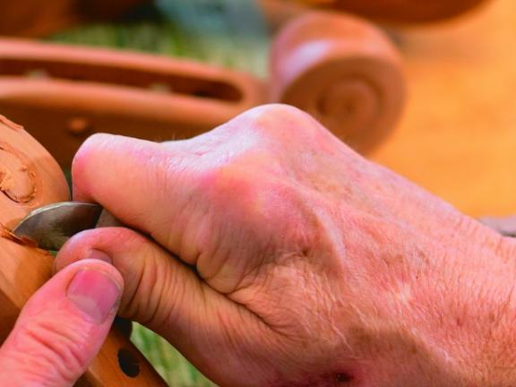A Kentucky artisan carves an instrument out of wood