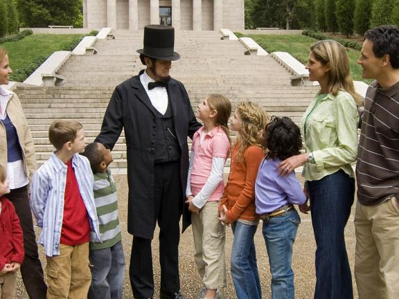 An Abraham Lincoln reenactor interacts with a group of visitors at Abraham Lincoln Birthplace National Historical Park
