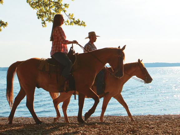 A couple goes horseback riding along a lake in Kentucky