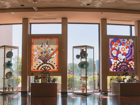 A panoramic image of the inside of the National Quilt Museum in Paducah, with large quilts hanging in front of windows