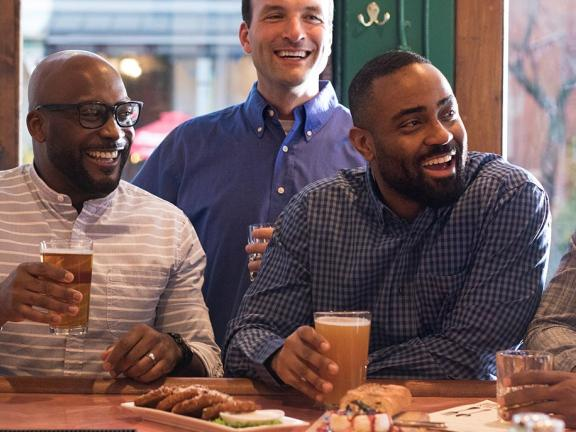 A group of male friends gather around a bar with beers in Kentucky