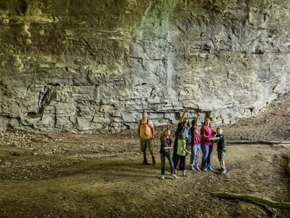 A family is dwarfed by the inside of a massive cave in the Kentucky Appalachians