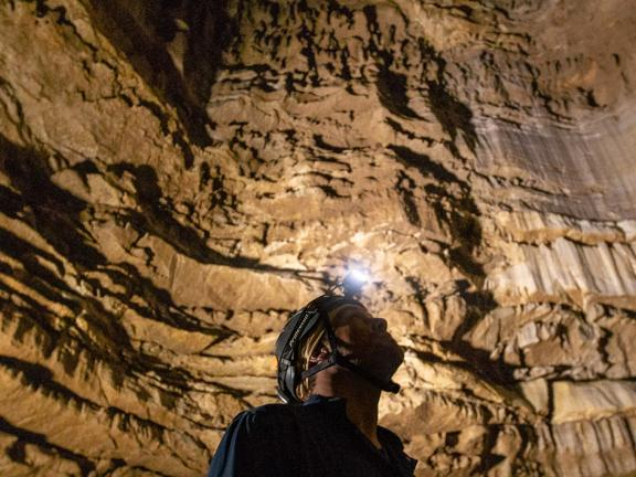 man with headlamp inside cave
