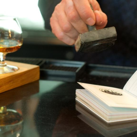 A bartender stamps a passport on the Louisville Urban Bourbon Trail