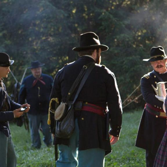 A group of costumed Civil War reenactors gather on a battlefield