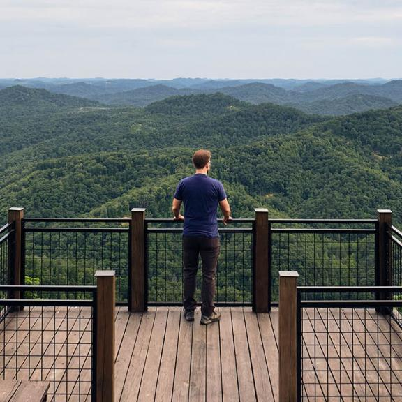 A man looks out at a mountain vista at a scenic overlook in Kentucky