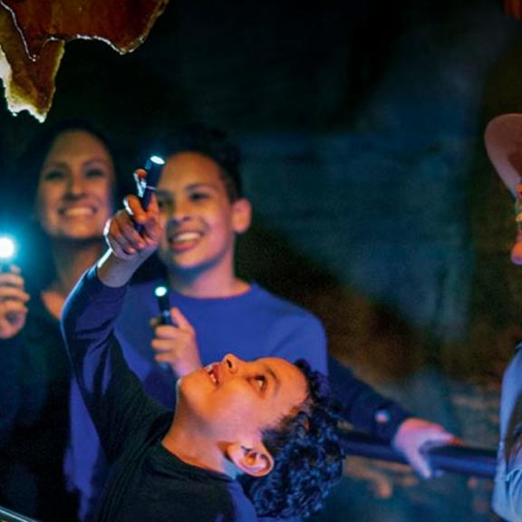 A family shines flashlights inside of Mammoth Cave park, along with a Park Ranger