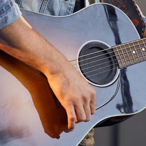 A close up of J.D. Shelburne's hand strumming his guitar