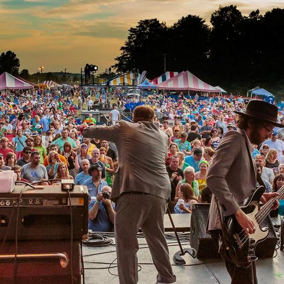 A band performs on a stage in front of a huge crowd at a Kentucky music festival