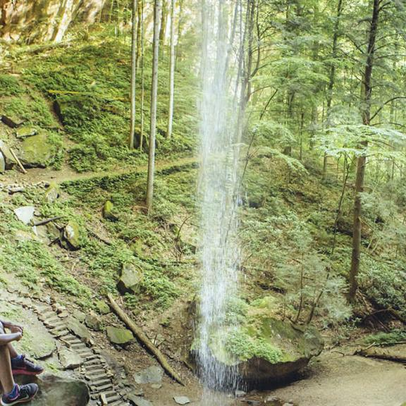 Two girls hike behind a waterfall in Kentucky