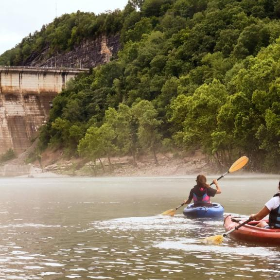 Two kayakers paddle near a Kentucky dam