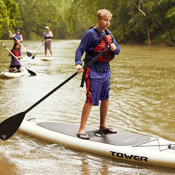 A boy and his family go stand-up paddleboarding in the Kentucky trail town of Livingston