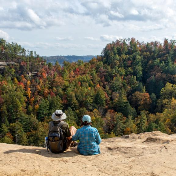 couple sitting at natural bridge in front of view