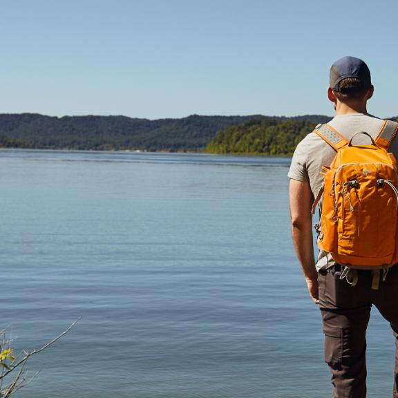 Guy wearing orange backpack standing with girl sitting down next to Cave Run Lake