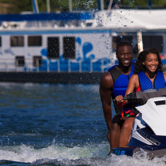 African American couple on jetski in front of houseboat on Lake Cumberland