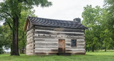 The historic Col. Charles Young Birthplace, a rustic cabin surrounded by trees