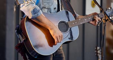 A closeup of musician J.D. Shelburne's black guitar, with his hand on the strings