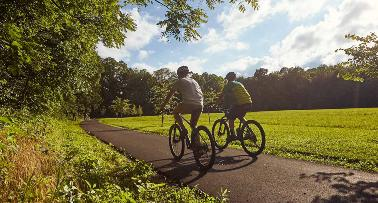 Two men bike on a paved path through a greenspace in Kentucky