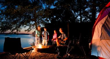 A family camps at a lakeside campground around a campfire at night