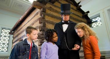 An Abraham Lincoln actor in period costume engages with a group of young children at the Abraham Lincoln Birthplace National Historical Park