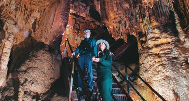 Two people stand inside a cavern at Mammoth Cave