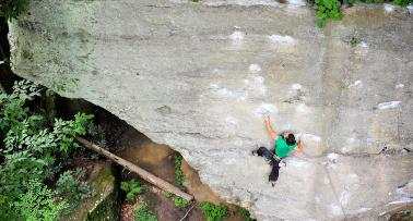 A female climber scales the side of a rock face at Red River Gorge in Kentucky